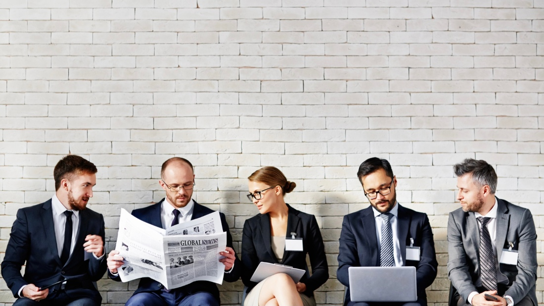 Five business people sitting along a wall