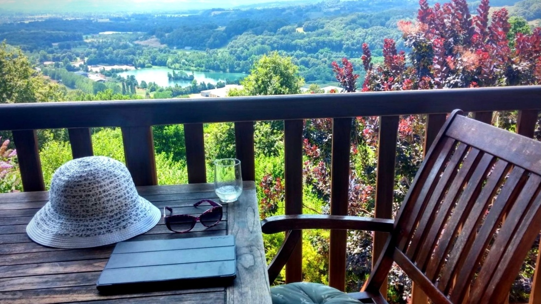 Picture of chair, notpad and drink on a balcony overlooking a view.