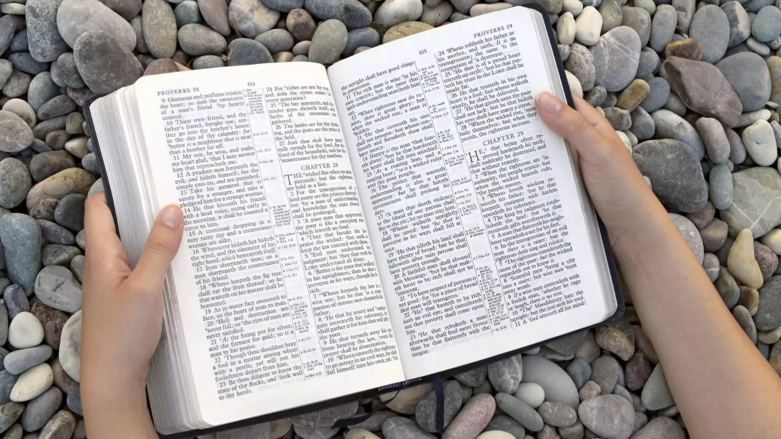 Picture of bible open at Proverbs, resting on some stones