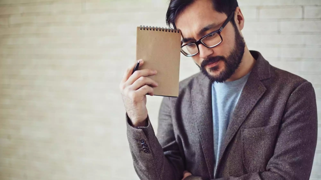 Pixture of man holding notebook trying to rememeber