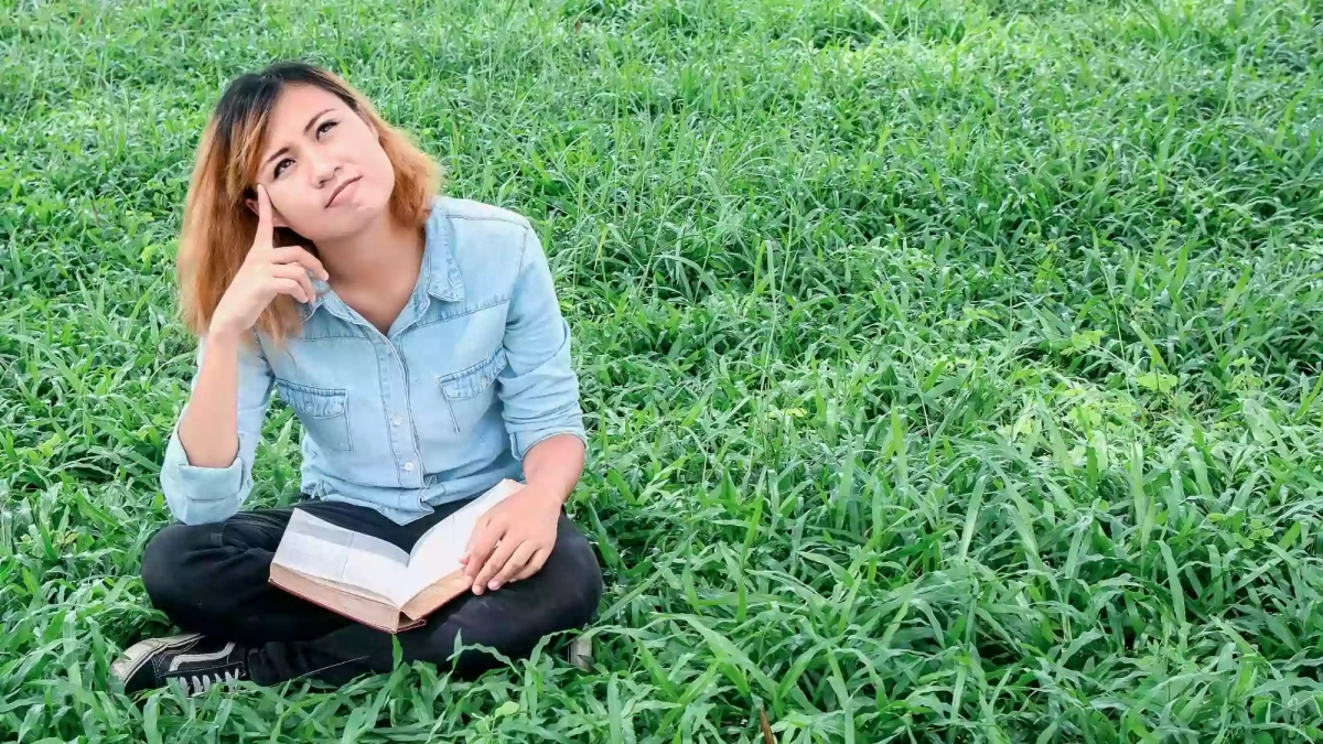 Pictufre of lady with a book, sitting on the grass
