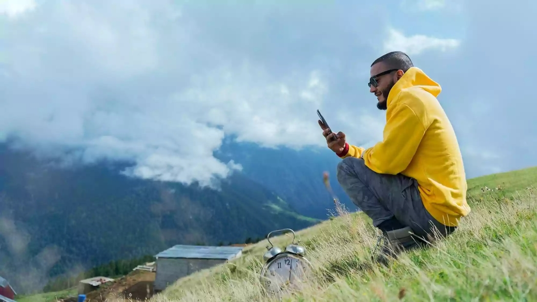 Picture of man sitting on a mountain taking a selfie